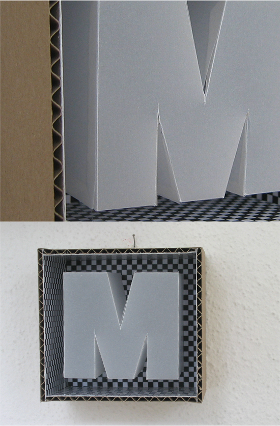 Cardboard box: M with checkerboard